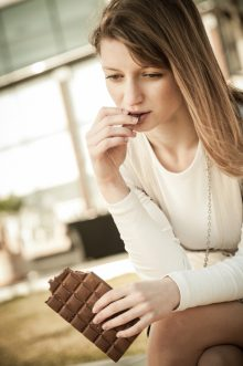 Depression - outdoor portrait of young worried woman eating chocolate